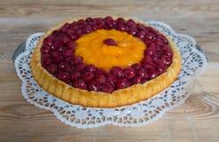 Queque de frutas con las cerezas y las mandarinas en la madera rústica Foto de archivo
