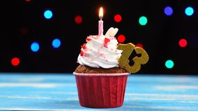 Queque delicioso do aniversário com vela e número de queimadura 13 no fundo borrado colorido das luzes video estoque