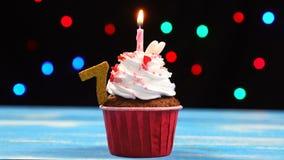 Queque delicioso do aniversário com vela e número de queimadura 7 no fundo borrado colorido das luzes filme