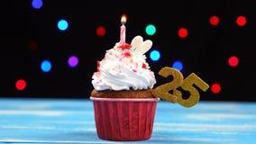 Queque delicioso do aniversário com vela e número de queimadura 25 no fundo borrado colorido das luzes filme