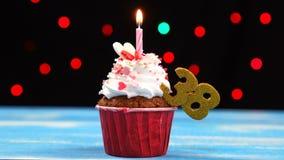 Queque delicioso do aniversário com vela e número de queimadura 38 no fundo borrado colorido das luzes filme
