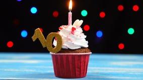 Queque delicioso do aniversário com vela e número de queimadura 10 no fundo borrado colorido das luzes filme