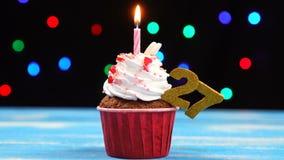 Queque delicioso do aniversário com vela e número de queimadura 27 no fundo borrado colorido das luzes vídeos de arquivo