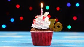 Queque delicioso do aniversário com vela e número de queimadura 19 no fundo borrado colorido das luzes video estoque