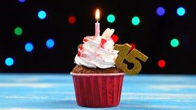 Queque delicioso do aniversário com vela e número de queimadura 15 no fundo borrado colorido das luzes video estoque