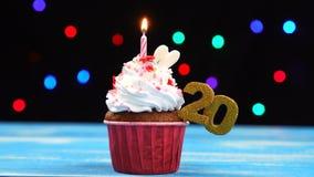 Queque delicioso do aniversário com vela e número de queimadura 20 no fundo borrado colorido das luzes filme
