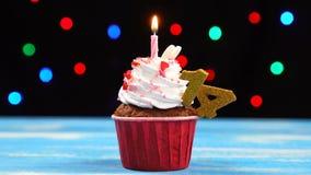 Queque delicioso do aniversário com vela e número de queimadura 14 no fundo borrado colorido das luzes video estoque