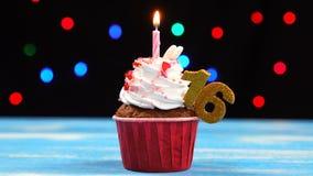 Queque delicioso do aniversário com vela e número de queimadura 16 no fundo borrado colorido das luzes filme