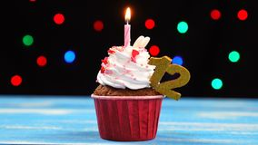Queque delicioso do aniversário com vela e número de queimadura 12 no fundo borrado colorido das luzes filme
