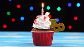 Queque delicioso do aniversário com vela e número de queimadura 18 no fundo borrado colorido das luzes filme