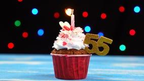Queque delicioso do aniversário com vela e número de queimadura 55 no fundo borrado colorido das luzes vídeos de arquivo