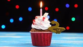 Queque delicioso do aniversário com vela e número de queimadura 24 no fundo borrado colorido das luzes filme