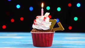 Queque delicioso do aniversário com vela e número de queimadura 17 no fundo borrado colorido das luzes video estoque