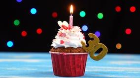 Queque delicioso do aniversário com vela e número de queimadura 30 no fundo borrado colorido das luzes vídeos de arquivo