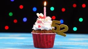 Queque delicioso do aniversário com vela e número de queimadura 52 no fundo borrado colorido das luzes filme