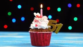 Queque delicioso do aniversário com vela e número de queimadura 51 no fundo borrado colorido das luzes vídeos de arquivo