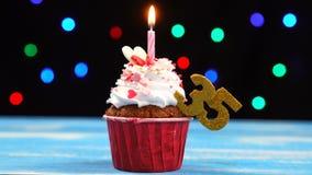 Queque delicioso do aniversário com vela e número de queimadura 35 no fundo borrado colorido das luzes vídeos de arquivo