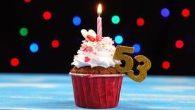 Queque delicioso do aniversário com vela e número de queimadura 53 no fundo borrado colorido das luzes filme