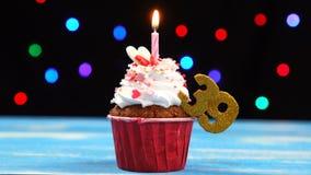 Queque delicioso do aniversário com vela e número de queimadura 39 no fundo borrado colorido das luzes vídeos de arquivo
