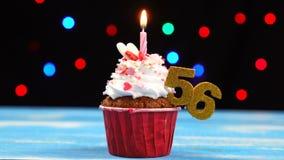 Queque delicioso do aniversário com vela e número de queimadura 56 no fundo borrado colorido das luzes filme