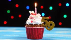 Queque delicioso do aniversário com vela e número de queimadura 59 no fundo borrado colorido das luzes video estoque