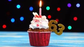 Queque delicioso do aniversário com vela e número de queimadura 63 no fundo borrado colorido das luzes video estoque