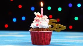 Queque delicioso do aniversário com vela e número de queimadura 54 no fundo borrado colorido das luzes filme