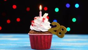 Queque delicioso do aniversário com vela e número de queimadura 28 no fundo borrado colorido das luzes video estoque