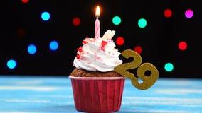 Queque delicioso do aniversário com vela e número de queimadura 29 no fundo borrado colorido das luzes filme