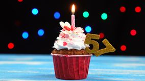 Queque delicioso do aniversário com vela e número de queimadura 57 no fundo borrado colorido das luzes vídeos de arquivo