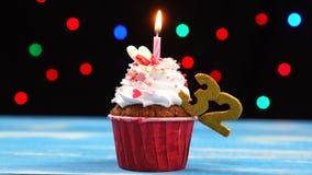 Queque delicioso do aniversário com vela e número de queimadura 32 no fundo borrado colorido das luzes filme