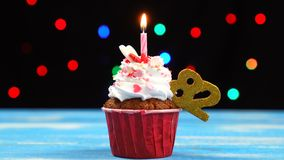 Queque delicioso do aniversário com vela e número de queimadura 82 no fundo borrado colorido das luzes video estoque