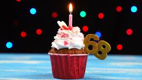 Queque delicioso do aniversário com vela e número de queimadura 68 no fundo borrado colorido das luzes vídeos de arquivo