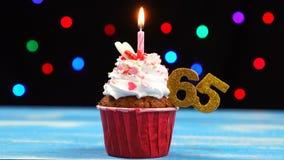 Queque delicioso do aniversário com vela e número de queimadura 65 no fundo borrado colorido das luzes vídeos de arquivo