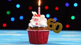 Queque delicioso do aniversário com vela e número de queimadura 60 no fundo borrado colorido das luzes filme
