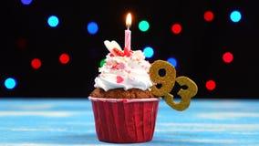 Queque delicioso do aniversário com vela e número de queimadura 93 no fundo borrado colorido das luzes vídeos de arquivo