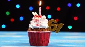 Queque delicioso do aniversário com vela e número de queimadura 61 no fundo borrado colorido das luzes filme