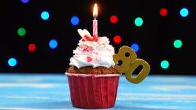Queque delicioso do aniversário com vela e número de queimadura 80 no fundo borrado colorido das luzes vídeos de arquivo