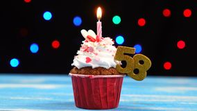 Queque delicioso do aniversário com vela e número de queimadura 58 no fundo borrado colorido das luzes vídeos de arquivo