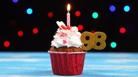 Queque delicioso do aniversário com vela e número de queimadura 98 no fundo borrado colorido das luzes vídeos de arquivo