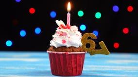 Queque delicioso do aniversário com vela e número de queimadura 67 no fundo borrado colorido das luzes video estoque