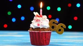 Queque delicioso do aniversário com vela e número de queimadura 66 no fundo borrado colorido das luzes filme