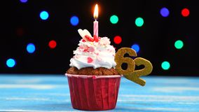 Queque delicioso do aniversário com vela e número de queimadura 62 no fundo borrado colorido das luzes vídeos de arquivo