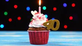 Queque delicioso do aniversário com vela e número de queimadura 40 no fundo borrado colorido das luzes filme