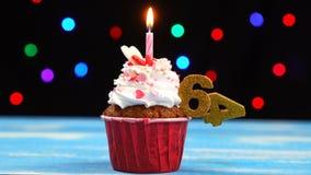 Queque delicioso do aniversário com vela e número de queimadura 64 no fundo borrado colorido das luzes filme