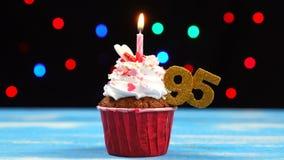 Queque delicioso do aniversário com vela e número de queimadura 95 no fundo borrado colorido das luzes vídeos de arquivo