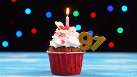 Queque delicioso do aniversário com vela e número de queimadura 91 no fundo borrado colorido das luzes filme