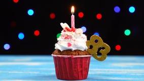 Queque delicioso do aniversário com vela e número de queimadura 83 no fundo borrado colorido das luzes filme