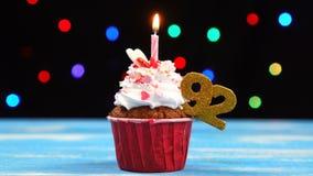 Queque delicioso do aniversário com vela e número de queimadura 92 no fundo borrado colorido das luzes filme