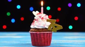 Queque delicioso do aniversário com vela e número de queimadura 74 no fundo borrado colorido das luzes filme